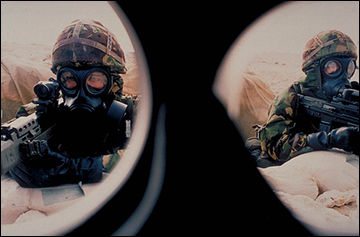 View through face mask of two soldiers wearing protective chemical weapons clothing holding guns in foxhole / ARMY IMAGE