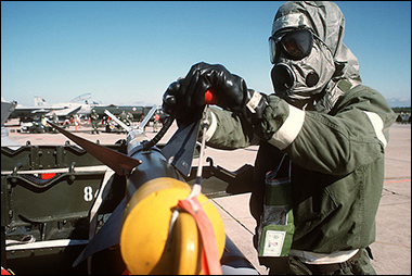 Army Sgt. checks fins on AIM-9 Sidewinder missile during simulated chemical warfare exercise.