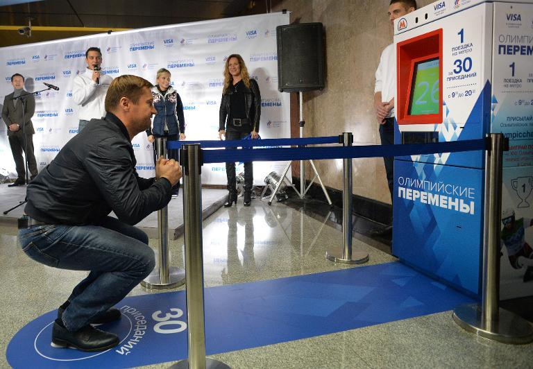 Olympic champion gymnast Alexei Nemov squats in front of a vending machine that sells the subway tickets for wquats instead of money during the machine's presentation at the Vystavochaya metro station in western Moscow, on November 8, 2013. (AFP Photo/Yuri Kadobnov)