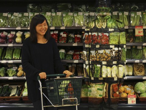 A woman laughs as she pushes a trolley past artist Liu Bolin during his demonstration to blend in with the vegetables on the shelves at a supermarket in Beijing, November 10, 2011. / Business Insider
