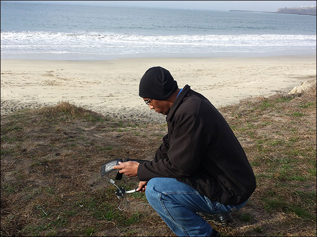 Infowars reporter Jakari Jackson takes Geiger counter measurements on Poplar Beach, Half Moon Bay, Cali.