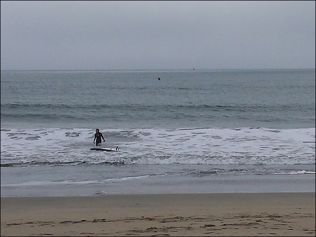 A third surfer enters the water blissfully unaware of the dangers the beach poses.