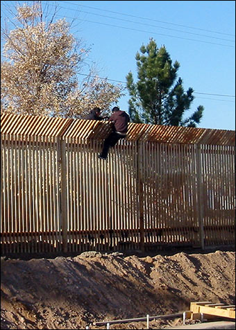 Two men scale a border fence between the U.S. and Mexico.