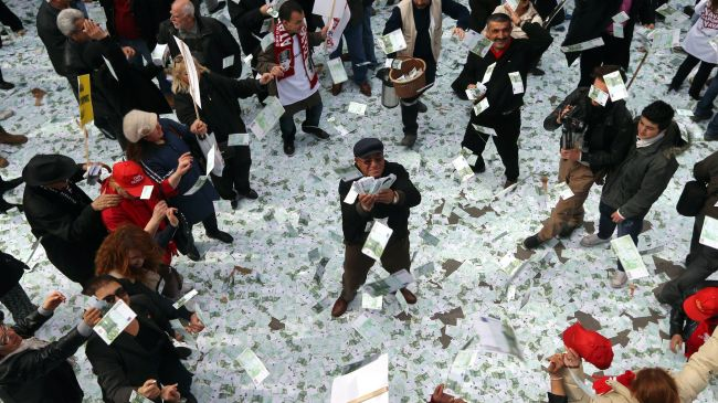 A man holds up a stack of fake euro notes during a demonstration against Turkey's prime minister in Ankara March 1, 2014.