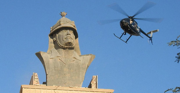 Blackwater helicopter over a bust of Saddam Hussein in Baghdad, Iraq. The mercenary group was implicated in the 2007 shooting in Baghdad's Nisour Square that killed 17 unarmed civilians, including women and children. Photo: Wikimedia Commons
