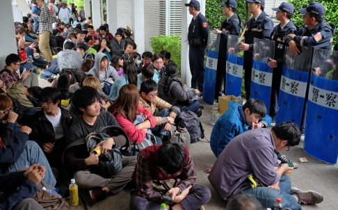 Hundreds of students and professors hold a sit-in outside parliament on Thursday as police guard the perimeter. Photo: AFP
