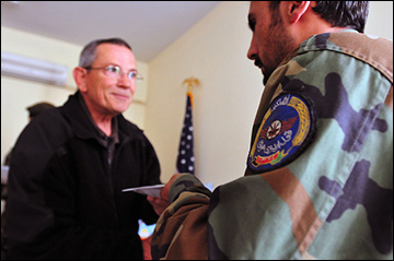 DynaCorp's Michael A. Benz gives a graduation certificate to an Afghan National Army soldier who successfully completed the Aircrew Chief course at Kabul Air Corps Training Center