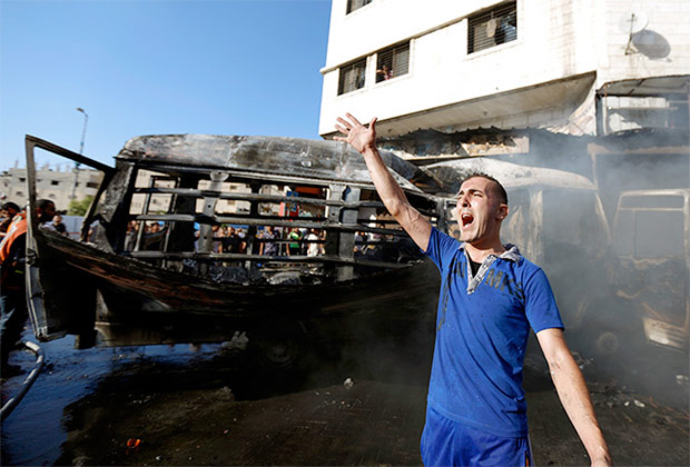 A Palestinian shouts slogans as firefighters try to extinguish the flames in a van, that was reportedly targeted by an Israeli military strike, in Gaza City on July 31, 2014. (AFP Photo / Mohammed Abed)