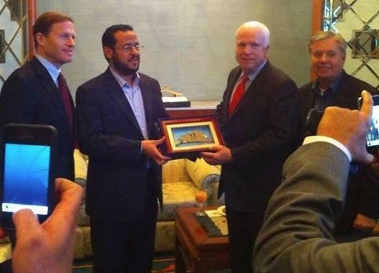Image: Al Qaeda's Abdelhakim Belhadj poses with US Senator John McCain. McCain's lobbying would play a part in securing Al Qaeda and its affiliates with sufficient arms to overthrow the secular government of Muammar Qaddafi in Libya. Soon after, these terrorists and their weapons would find their way to Syria via NATO-member Turkey.