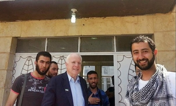 """Image: US Senator John McCain with members of the so-called """"Free Syrian Army."""" Several of the men pictured with McCain would end up committing horrific sectarian atrocities."""