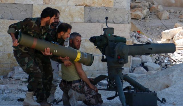 Image: Irregular war. Irregular troops. Terrorists in Syria load up a US-TOW anti-tank missile system. The United States has been training, arming, funding, and supplying terrorists fighting in Syria since 2011. A similar operation has left Libya divided and destroyed,  firmly in the hands of Al Qaeda.