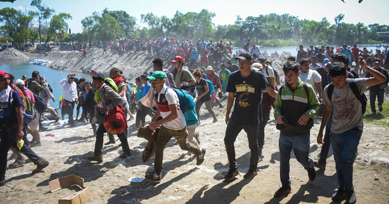 VIDEO: Thousands of migrants with luggage, strollers cross river to clash with Mexican troops